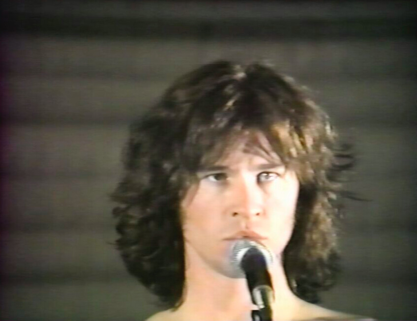 man with long brown hair at microphone in Val