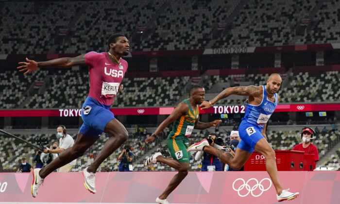 Lamont Jacobs (R) of Italy wins the men's the 100-meter final at the 2020 Summer Olympics in Tokyo, Japan, on Aug. 1, 2021. (David J. Phillip/AP Photo)