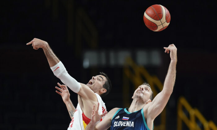 Spain's Alberto Abalde fights for a rebound with Slovenia's Zoran Dragic (30) during a men's basketball preliminary round game at the 2020 Summer Olympics in Saitama, Japan, on Aug. 1, 2021. (Charlie Neibergall/AP Photo)
