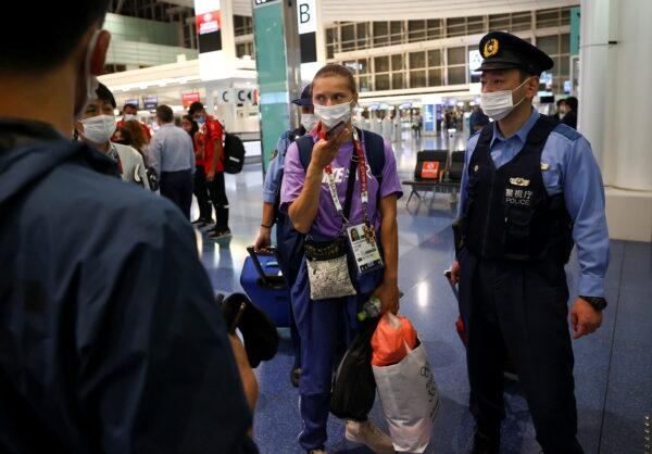 Belarusian sprinter Krystsina Tsimanouskaya is escorted by police officers at Haneda international airport in Tokyo