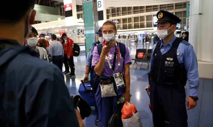 Belarusian sprinter Krystsina Tsimanouskaya is escorted by police officers at Haneda international airport in Tokyo, Japan, on Aug. 1, 2021. (Issei Kato/Reuters)
