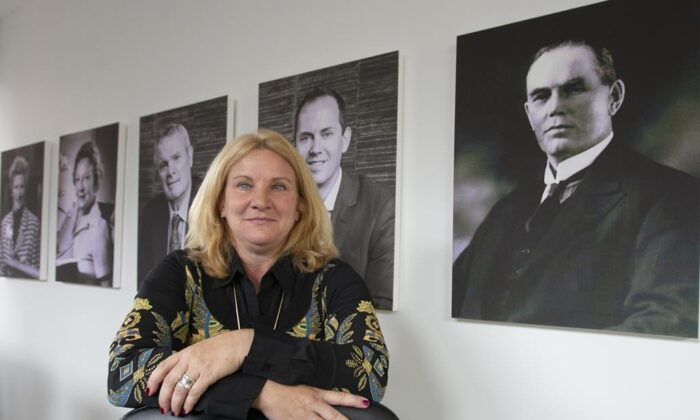 Elisabeth Ann Laett, Holt Xchange's managing partner, is seen in front of portraits of her family at the company's office in Montreal on July 30, 2021. (The Canadian Press/Ryan Remiorz)