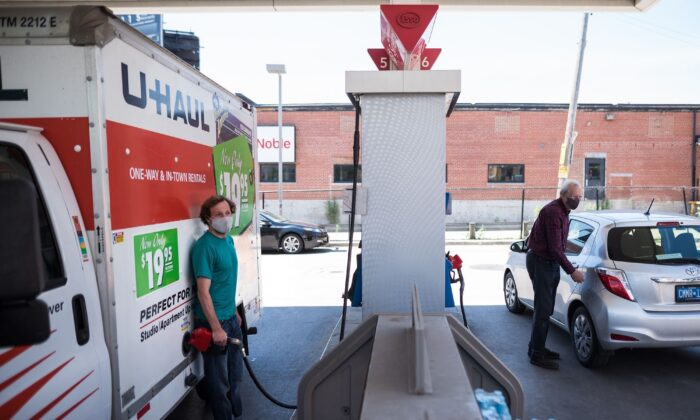 People pump gas at a gas station in Toronto on June 15, 2021. The prices of many goods and services are rising, including gasoline, with inflation standing at 3.1 percent in June 2021 according to the Bank of Canada's consumer price index. (The Canadian Press/ Tijana Martin)