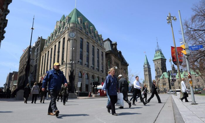 Pedestrians cross Elgin Street in view of Parliament Hill in Ottawa in a file photo. There's a strong likelihood Canadians will be heading to the polls in a federal election this fall. (The Canadian Press/Sean Kilpatrick)