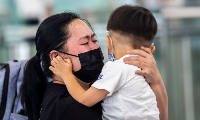 A woman is hugging a young child at the departure gates of Hong Kong's International Airport on July 19, 2021. (ISAAC LAWRENCE/AFP via Getty Images)