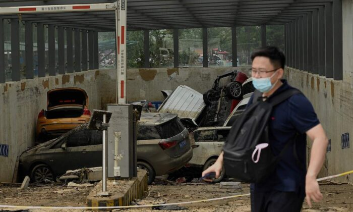 A man on July 24, 2021, walks past a car park with damaged vehicles stacked on each other following heavy rain which caused flooding days earlier that claimed at least 56 lives, in the city of Zhengzhou in China's Henan Province. (Noel Celis/AFP via Getty Images)