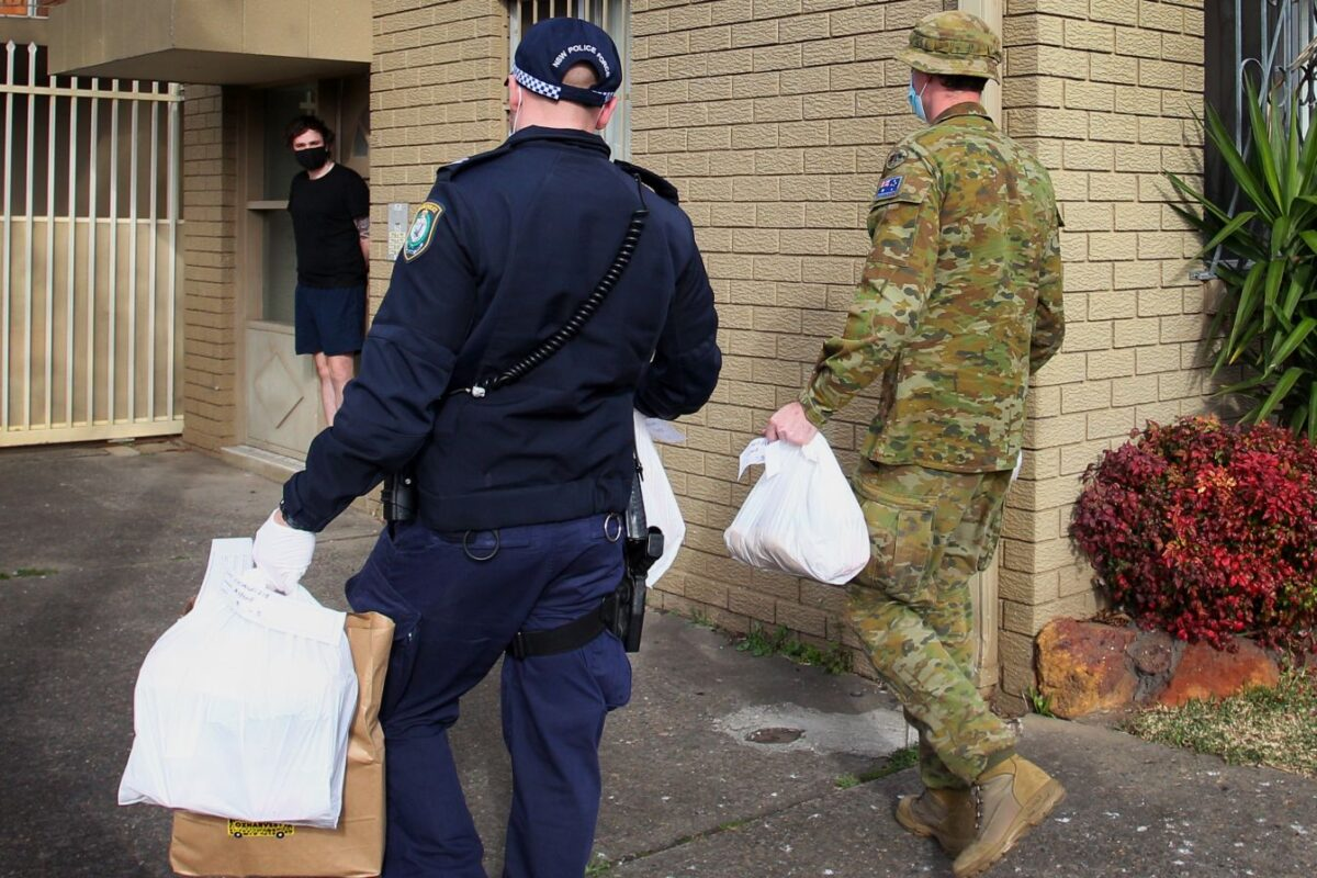 Australian Defence Force personnel and NSW police deliver food packages to people in lockdown in the Fairfield district in Sydney on Aug. 2, 2021. (Photo by Lisa Maree Williams/Getty Images)