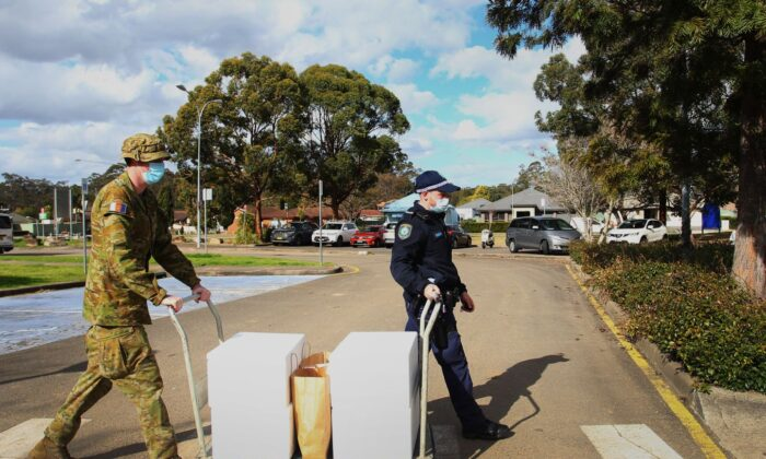 Australian Defence Force personnel and NSW police load food packages for delivery to people in lockdown at the Prairiewood Leisure Centre on Aug. 2, 2021 in Sydney, Australia. (Lisa Maree Williams/Getty Images)