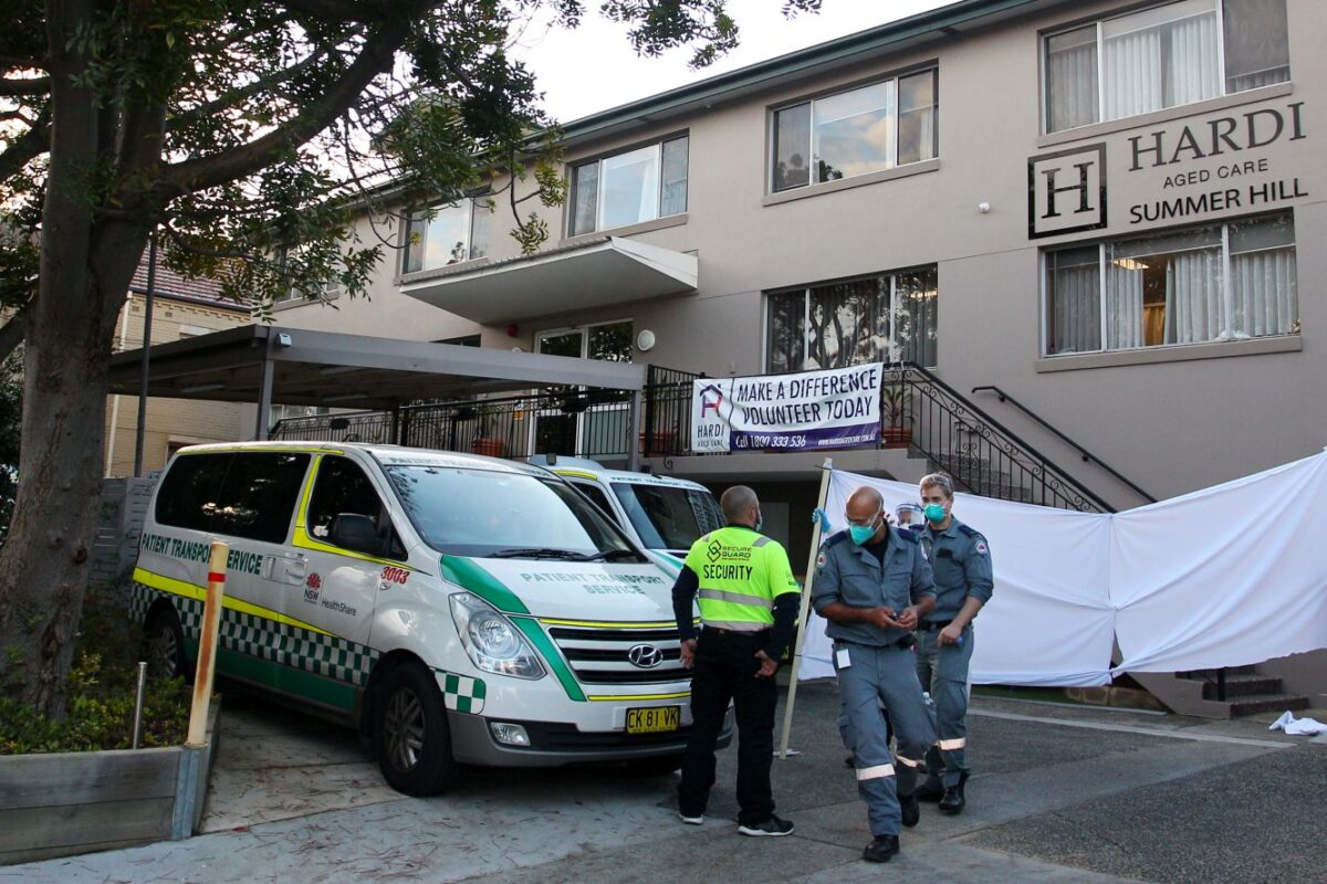 An ambulance officer and staff are seen at the entrance of the Hardi Aged Care Nursing Home Facility at Summer Hill in Sydney, on August 2, 2021. (Photo by Lisa Maree Williams/Getty Images)