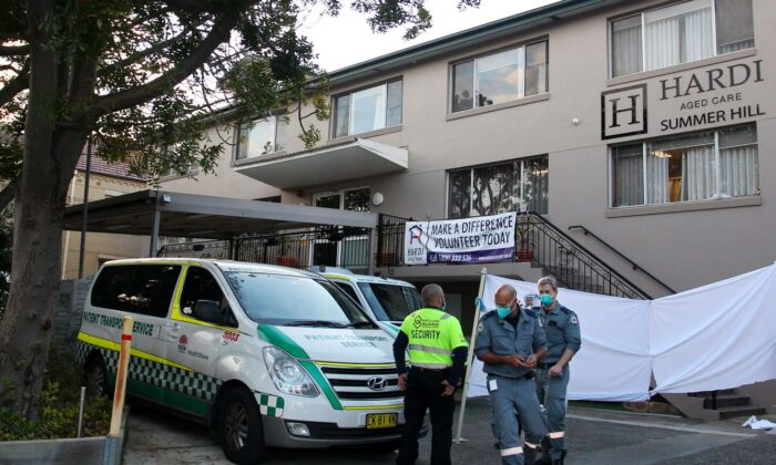 An ambulance officer and staff are seen at the entrance of the Hardi Aged Care Nursing Home Facility at Summer Hill in Sydney, Australia, on Aug. 2, 2021. (Lisa Maree Williams/Getty Images)