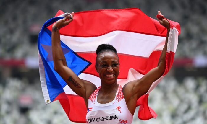 Jasmine Camacho-Quinn of Puerto Rico celebrates with her national flag after winning the women's 100 meters hurdles gold at Olympic Stadium in Tokyo, Japan, on Aug. 2, 2021. (Dylan Martinez/Reuters)