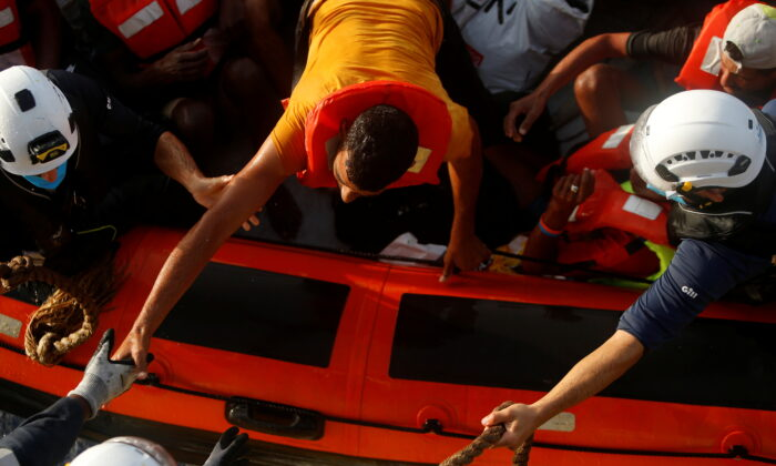 A migrant prepares to climb on board the German NGO migrant rescue ship Sea-Watch 3 from a rescue RHIB (rigid hulled inflatable boat) in international waters north of Libya, in the western Mediterranean Sea, on Aug. 2, 2021. (Darrin Zammit Lupi/Reuters)