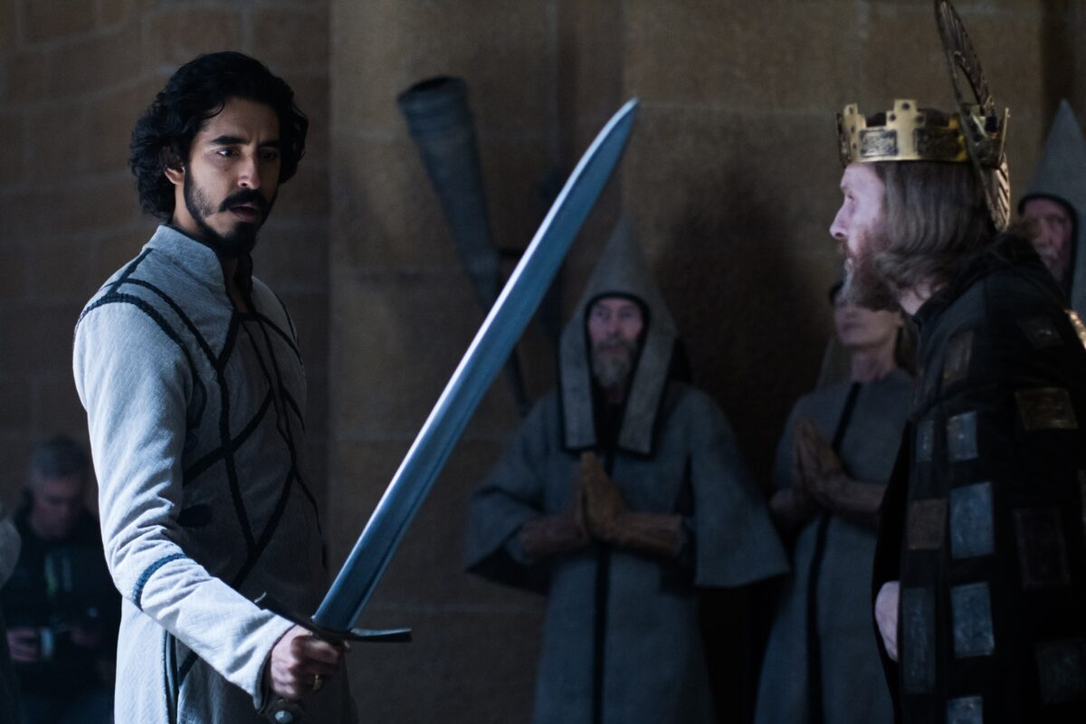 man with sword stands before a king inThe Green Knight