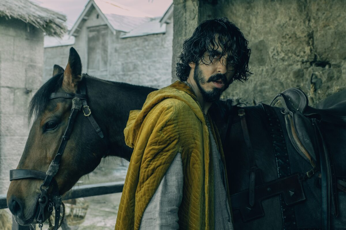 man in yellow robe with horse in The Green Knight