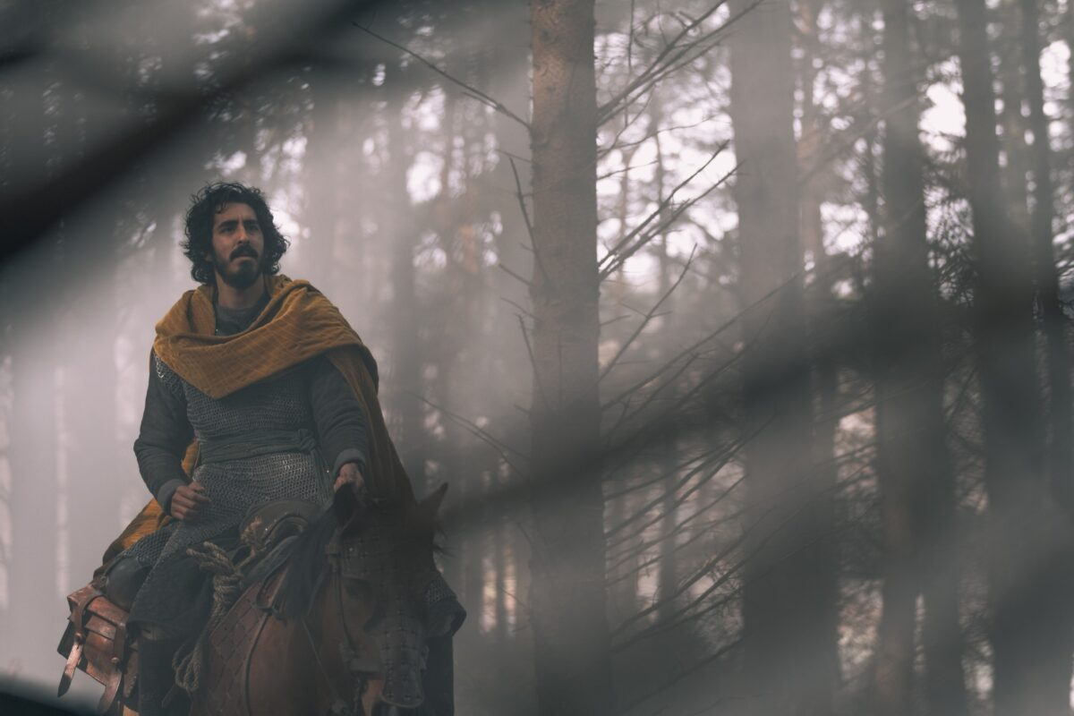 man in yellow robe riding horse inThe Green Knight