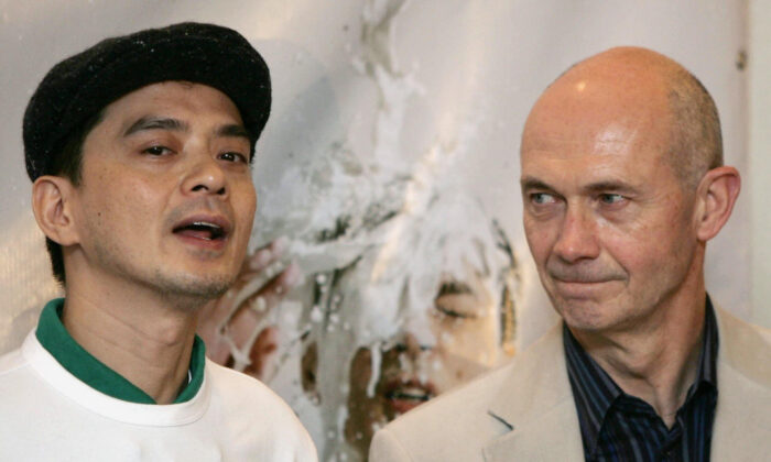 Chinese singer Anthony Wong (L) addresses the press before presenting a petition to WTO Director General Pascal Lamy (R) at the sixth WTO Ministerial Conference in Hong Kong on Dec. 12, 2005. (Mike Clarke/AFP via Getty Images)