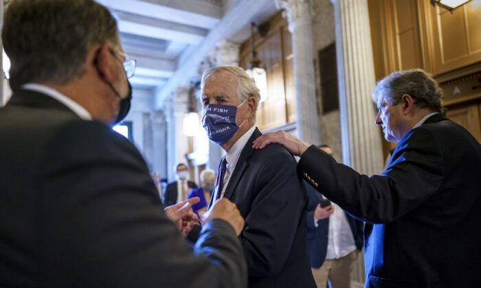 Sen. Angus King (I-Maine) (C) speaks with Sen. Gary Peters (D-Mich.) (L), while Sen. John Kennedy (R-La.) walks by (R), as the Senate votes to formally begin debate on a roughly $1 trillion infrastructure plan at the U.S. Capitol in Washington on July 30, 2021. (J. Scott Applewhite/AP Photo)