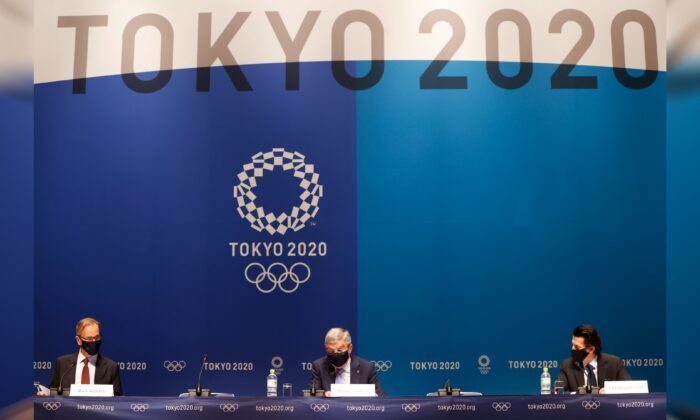 International Olympic Committee (IOC) President Thomas Bach with Director of Communications Mark Adams and Olympic Games Executive Director Christophe Dubi during the news conference in Tokyo, Japan, on July 17, 2021. (Phil Noble/Reuters)