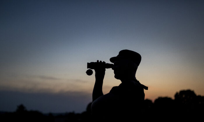 A member of the Lithuania State Border Guard Service looks through binoculars as he patrols on the border with Belarus, near the village of Purvenai, Lithuania, on July 9, 2021.  (Mindaugas Kulbis/AP Photo)