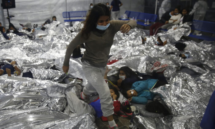 A minor walks over others inside a pod for females at the Department of Homeland Security holding facility run by the Customs and Border Patrol (CBP) in Donna, Texas, on March 30, 2021. (Dario Lopez-Mills/Pool/Getty Images)