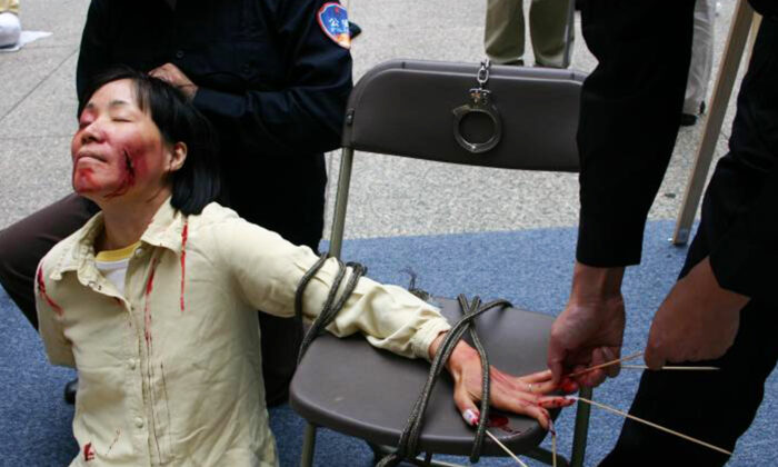 Reenactment of one of the torture methods employed by Chinese officials to coerce Falun Gong practitioners to renounce their faith.   (Minghui.org)