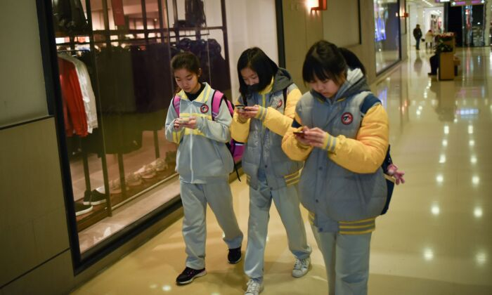 Students use their mobile phones while walking in a mall in Beijing, China on Jan. 26, 2018. (Wang Zhao/AFP via Getty Images)