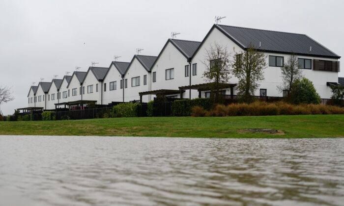 A flooded river flows next to a row of houses in Kaiapoi, New Zealand, on May 31, 2021. (Kai Schwoerer/Getty Images)