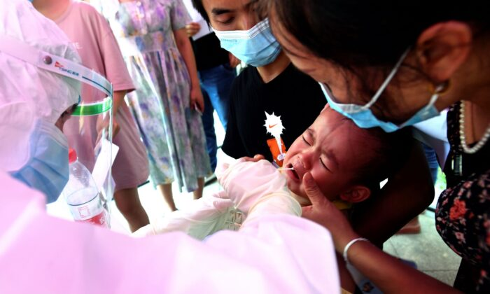 A medical worker takes swab samples from a child during mass testing for the CCP virus at a residential block in Wuhan, Hubei province, China, on Aug. 3, 2021. (Chinatopix via AP)