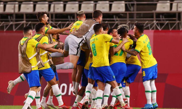 Brazil players celebrate winning the penalty shootout during the Tokyo 2020 Olympic Games men's semi-final football match between Mexico and Brazil at Ibaraki Kashima Stadium in Kashima city, Ibaraki, Japan, on Aug. 3, 2021. (Edgar Su/Reuters)