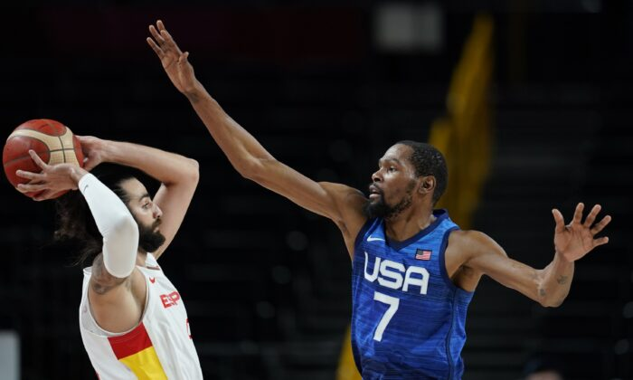 United States' Kevin Durant (7), right, covers Spain's Ricky Rubio (9), left, during men's basketball quarterfinal game at the 2020 Summer Olympics in Saitam, Japan on Aug. 3, 2021. (Charlie Neibergall/AP Photo)