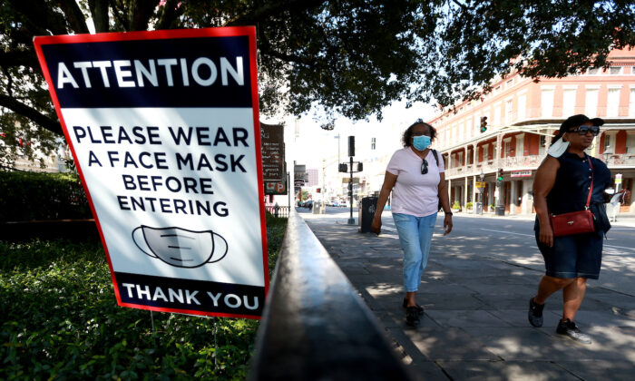 Visitors walk past mask signs along Decatur Street in the French Quarter in New Orleans, Louisiana, on July 14, 2020. (Sean Gardner/Getty Images)