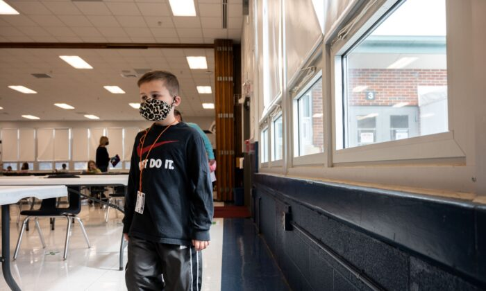 A masked student walks in line through the cafeteria at Medora Elementary School in Louisville, Ky., on March 17, 2021. (Jon Cherry/Getty Images)