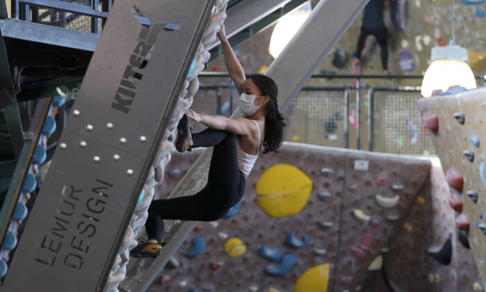 A person wears a protective face mask while working out at Planet Granite climbing gym in San Francisco, on March 4, 2021. (AP Photo/Jeff Chiu)