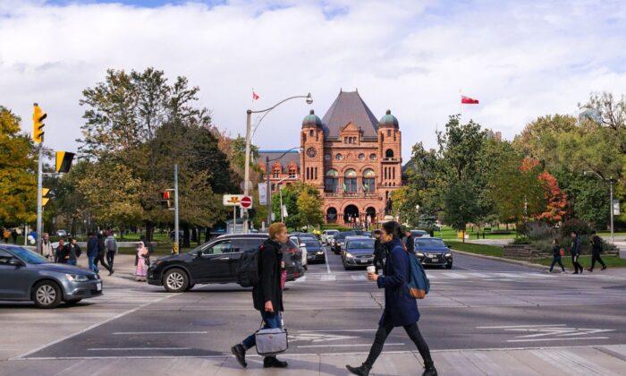 Pedestrians cross University Avenue in front of the Ontario Legislative Building in Toronto in a file photo. (Vadim Rodnev/Shutterstock)