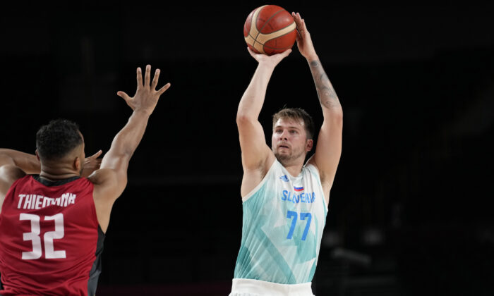 Slovenia's Luka Doncic (77), right, shoots over Germany's Johannes Thiemann (32) during men's basketball quarterfinal game at the 2020 Summer Olympics, in Saitama, Japan, on Aug. 3, 2021. (Eric Gay/AP Photo)