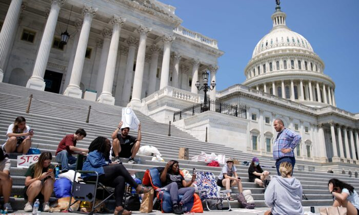 Rep. Cori Bush (D-Mo.) holds up her phone while live streaming from the chair she spent the night in to highlight the upcoming expiration of the pandemic-related federal moratorium on residential evictions on the steps of the Capitol in Washington on July 31, 2021. (Elizabeth Frantz/Reuters)