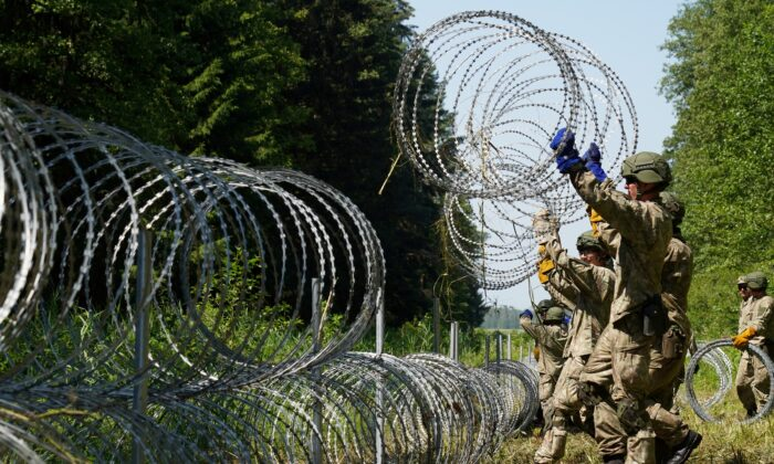 Lithuanian army soldiers install razor wire on the border with Belarus in Druskininkai, Lithuania, on July 9, 2021. (Janis Laizans/Reuters)