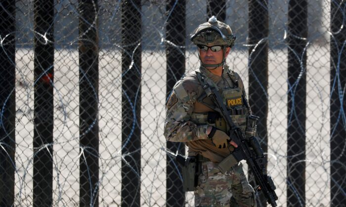 An armed U.S. Customs and Border Patrol agent stands watch at the border fence next to the beach in Tijuana, at the Border State Park in San Diego, Calif., on Nov. 16, 2018. (Mike Blake/File Photo/Reuters)