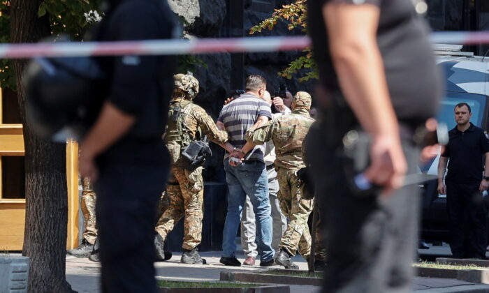 Law enforcement officers detain a man who, according to the head of the National Police, forced his way into Ukraine's main government building and threatened to detonate a grenade, in Kyiv, Ukraine, on Aug. 4, 2021. (Serhii Nuzhnenko/Reuters)