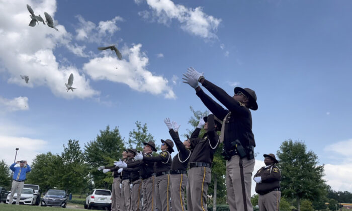 Sheriff's deputies release white doves for the young victims of a fatal car crash outside a church where the public memorial service was held, in Auburn, Ala., on July 15, 2021. (Kim Chandler/File/AP Photo)