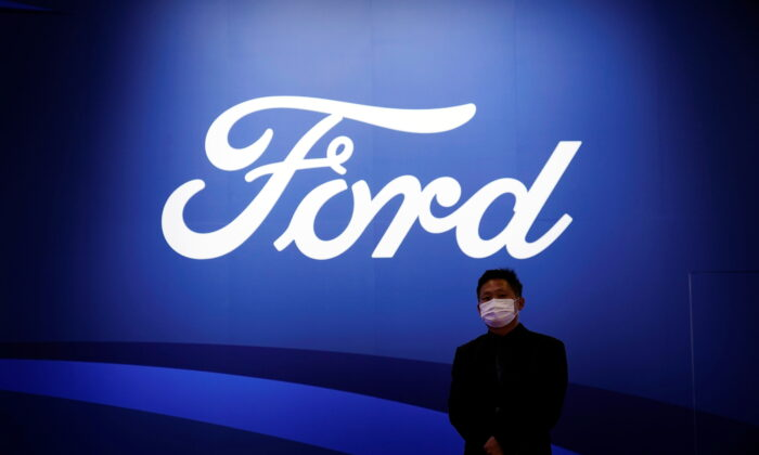 A man stands near the Ford logo during a media day for the Auto Shanghai show in Shanghai, China, on April 19, 2021. (Aly Song/Reuters)