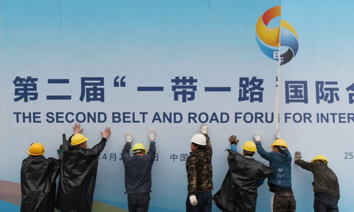 Workers take down a Belt and Road Forum panel outside the venue of the forum in Beijing on April 27, 2019. (Greg Baker/AFP via Getty Images)