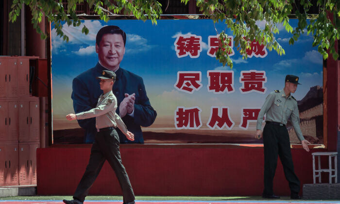 Soldiers are seen near a poster of Chinese leader Xi Jinping next to the entrance to the Forbidden City in Beijing on May 18, 2020. (Nicolas Asfouri/AFP via Getty Images)