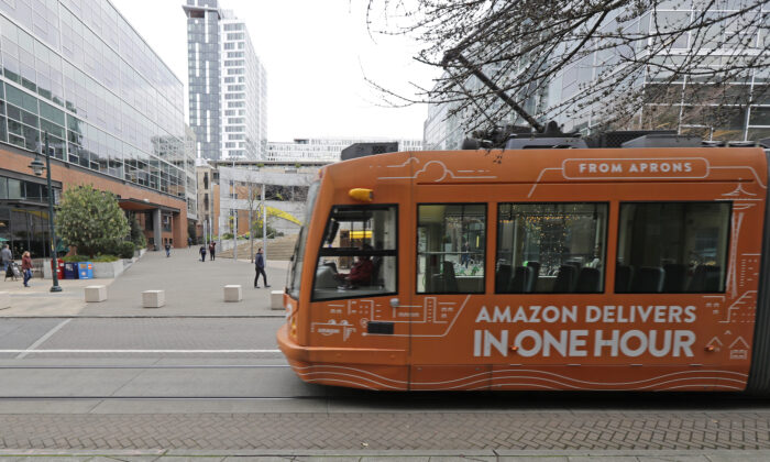 A South Lake Union streetcar with an advertisement for Amazon.com's same-day delivery service passes by an Amazon office building in Seattle's South Lake Union neighborhood, Wash., on Nov. 13, 2018. (Ted S. Warren/AP Photo)