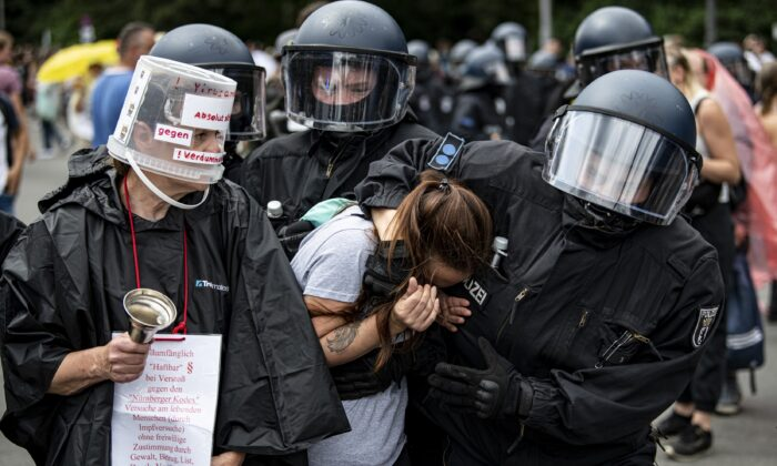 Police arrest a demonstrator at a protest against anti-COVID-19 measures, at the Victory Column, in Berlin on Aug. 1, 2021. (Fabian Sommer/dpa via AP)