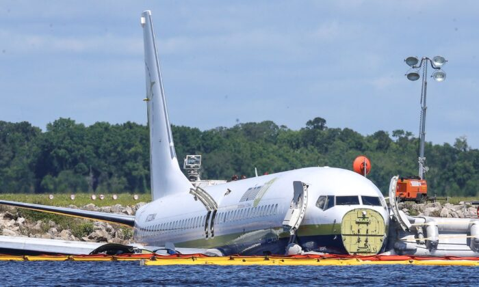A charter plane carrying 143 people and traveling from Cuba to north Florida sits in a river at the end of a runway in Jacksonville, Fla., on May 4, 2019. (Gary McCullough/File/AP Photo)