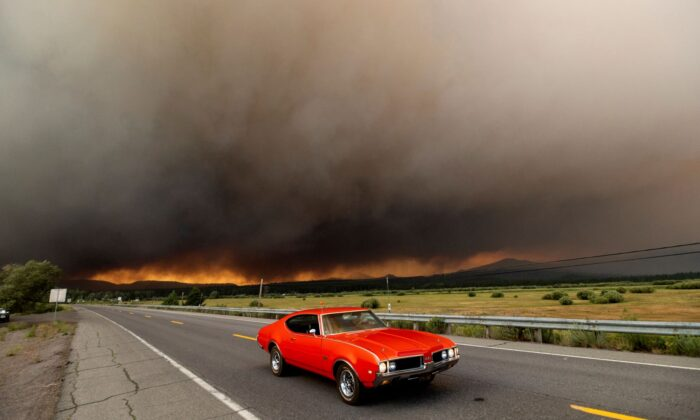 A car leaves Chester, Calif., which is under mandatory evacuation orders, as the Dixie Fire burns on the edge of town on Aug. 4, 2021. (Noah Berger/AP Photo)