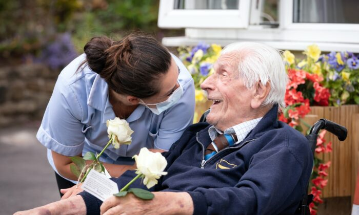 """Health Care Assistant Rose Waddington and ninety-eight-year-old resident John Kykot are pictured with """"thank you"""" white roses that were presented to them by the Mayor of West Yorkshire Tracy Brabin at Norwood House Nursing Home in Keighley, England, on July 4, 2021. (Danny Lawson/PA)"""