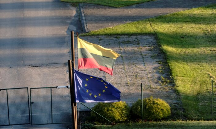 Lithuanian and European Union flags flutter at the Lithuanian border guards unit headquarters near Adutiskis, Lithuania, on June 15, 2021. (Ints Kalnins/Reuters)