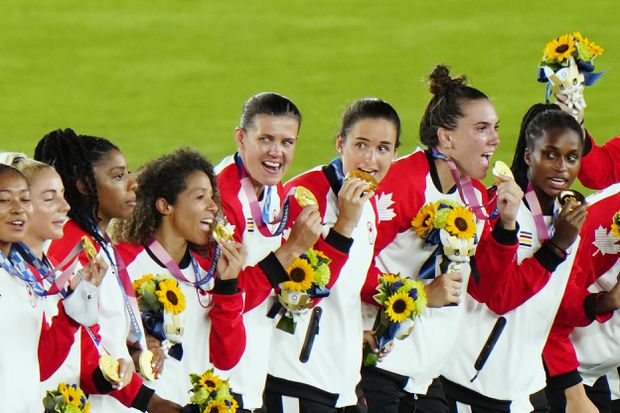 Canadian players celebrate with their gold medals after defeating Sweden in the penalty shootout in the women's soccer final during the summer Tokyo Olympics in Yokohama, Japan, on Aug. 6, 2021. (The Canadian Press/Frank Gunn)